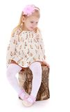 Adorable little girl is sitting on birch stump Stock Photo