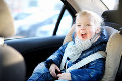 Adorable little girl sitting in a car seat Royalty Free Stock Photos