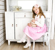 Adorable little girl sitting on chair with gift box Stock Image