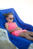Adorable little girl sitting on chair at tropical Royalty Free Stock Photography