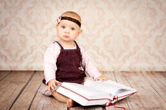 Adorable little girl sitting on the floor and holding big book Royalty Free Stock Image