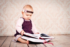 Adorable little girl sitting on the floor and holding big book Royalty Free Stock Images