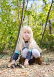 Adorable Little Girl Sitting on Forest Ground Stock Photos