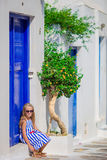Adorable little girl sitting in front of blue door outdoors at typical greek traditional village on Mykonos in Greece Stock Images