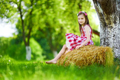 Adorable little girl sitting on a haystack in apple tree garden Royalty Free Stock Image