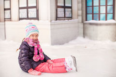 Adorable little girl sitting on ice with skates Stock Photos