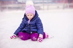 Adorable little girl sitting on ice with skates Stock Image