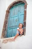 Adorable little girl sitting near blue door of old Stock Photos