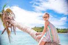 Adorable little girl sitting on palm tree during summer vacation on white beach Royalty Free Stock Photos