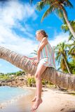 Adorable little girl sitting on palm tree during summer vacation on white beach Royalty Free Stock Image