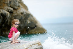 Adorable little girl sitting on a rock Royalty Free Stock Image