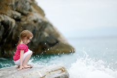 Adorable little girl sitting on a rock Royalty Free Stock Photography