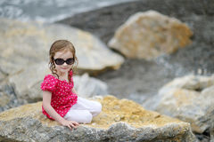 Adorable little girl sitting on a rock Royalty Free Stock Images