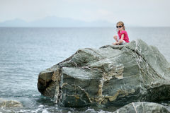 Adorable little girl sitting on a rock Stock Photo