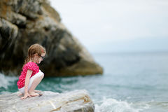 Adorable little girl sitting on a rock Stock Image