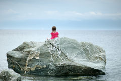 Adorable little girl sitting on a rock Stock Images