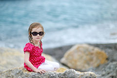 Adorable little girl sitting on a rock Royalty Free Stock Photos