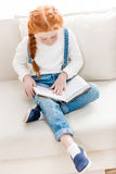 Adorable little girl sitting on sofa and reading book Royalty Free Stock Photography