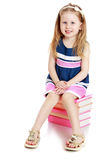 Adorable little girl sitting on a stack of books Stock Photos