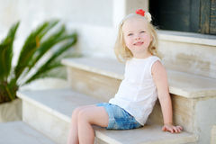 Adorable little girl sitting on stairs Stock Image
