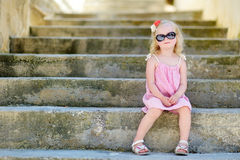 Adorable little girl sitting on stairs Royalty Free Stock Image
