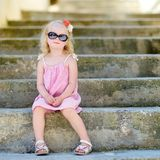 Adorable little girl sitting on stairs Royalty Free Stock Photos