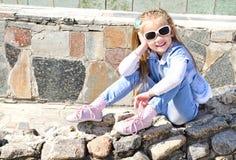 Adorable little girl sitting on stones Stock Photos