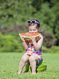 Adorable little girl sitting on a watermelon. Eating a slice Royalty Free Stock Image