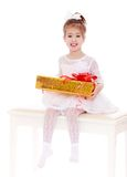 Adorable little girl is sitting on a white couch. To keep in the hands of a big box with a gift.Isolated on white background, Lotus Children's Center Stock Photography