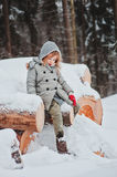 Adorable little girl sitting on wood log in winter snowy forest Stock Image