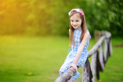 Adorable little girl sitting on a wooden fence on beautiful spring day Stock Photo