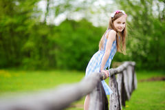 Adorable little girl sitting on a wooden fence on beautiful spring day Stock Image