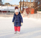 Adorable little girl in the skate on white ice Royalty Free Stock Photo