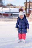Adorable little girl in the skate on white ice Royalty Free Stock Photos
