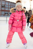 Adorable little girl skating on the ice-rink Stock Photography