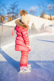 Adorable little girl skating on the ice-rink Royalty Free Stock Images