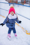 Adorable little girl skating on the ice-rink Stock Image