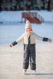 Adorable little girl skating on the ice rink outdoors. Adorable little girl skating on the ice-rink Stock Images