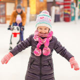 Adorable little girl on skating rink with father Royalty Free Stock Image