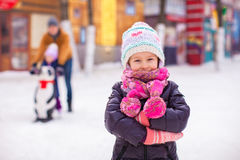 Adorable little girl on skating rink with father Stock Photos