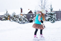 Adorable little girl skating in winter snowy day Stock Photos