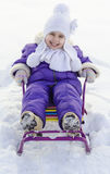 Adorable little girl on a sled at winter sunny day. Happy smiling child, boy or girl, sledging in fresh snow in winter Stock Photo