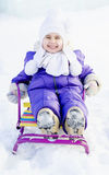 Adorable little girl on a sled at winter sunny day. Happy smiling child, boy or girl, sledging in fresh snow in winter Royalty Free Stock Photo