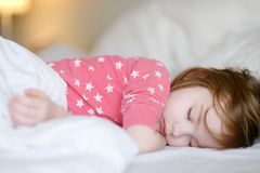 Adorable little girl sleeping. In a bed Royalty Free Stock Photos