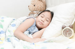 Adorable little girl sleeping in the bed. Adorable little girl sleeping in the bed with alarm clock Stock Image
