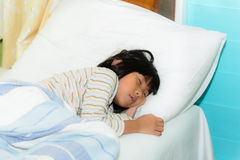 Adorable little girl sleeping in a bed. Adorable little Asian girl sleeping in a bed at home Royalty Free Stock Images