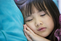 Adorable little girl sleeping in a bed. Close up of little asian girl sleeping in a bed Royalty Free Stock Image