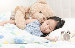 Adorable little girl sleeping in the bed. With her teddy bear Stock Photos
