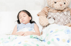 Adorable little girl sleeping in the bed. With her teddy bear Royalty Free Stock Image