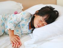 Adorable little girl sleeping in the bed with her toy.  Stock Images